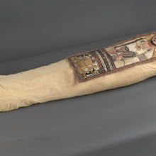 <p><em>Cartonnage and Mummy of an Anonymous Man</em>. Egypt, excavated in Deir el Bahri. Roman Period, 3rd century <small>C.E.</small> Linen, plaster, paint, organic materials; cartonnage: 13<sup>1</sup>⁄<sub>4</sub> x 35<sup>7</sup>⁄<sub>16</sub> in. (33.7 × 90 cm); mummy, approximately: 8 × 20 × 62 in. (20.3 × 50.8 × 157.5 cm). Brooklyn Museum, Charles Edwin Wilbour Fund, 52.128a–e</p>