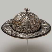 <p>Possibly Aymara artist. <em>Festival Hat</em>, 18th century. Repoussé silver plaques on velvet, glass beads, wire, 4<sup>15</sup>/<sub>16</sub> × 13<sup>1</sup>/<sub>4</sub> × 13<sup>1</sup>/<sub>4</sub> in. (12.5 × 33.7 × 33.7 cm). Museum Expedition 1941, Frank L. Babbott Fund, 41.1275.274c</p>