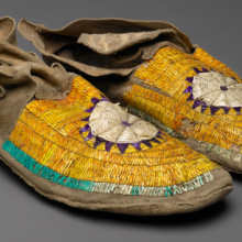 <p>Sioux, Hidatsa, or Arikara artist. <em>Man's Moccasins</em>, circa 1882. Hide, dyed porcupine twill, 10<sup>7</sup>/<sub>16</sub> × 3<sup>15</sup>/<sub>16</sub> in. (26.5 × 10 cm). Brooklyn Museum; Anonymous gift in memory of Dr. Harlow Brooks, 43.201.66a–b. (Photo: Brooklyn Museum)</p>