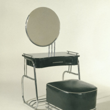 <p><em>Vanity with Mirror and Stool</em>. Kem Weber (American, born Germany, 1889–1963). Made by Lloyd Manufacturing Company. Menominee, Michigan, 1934. Chrome-plated tubular steel, wood, glass, upholstery, vanity: 55 × 33 × 191⁄2 in. (139.7 × 83.8 × 49.5 cm), stool: 17<sup>1</sup>⁄<sub>2</sub> x 21 × 22<sup>1</sup>⁄<sub>2</sub> in. (44.5 × 53.3 × 57.2 cm). Brooklyn Museum, Modernism Benefit Fund, 87.123.1a–b and 87.123.2</p>