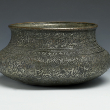 <p><i>Wine Bowl Inscribed with the Names of the Twelve Shiʿa Imams</i>. Iran, Safavid, late 16th–early 17th century. Copper; cast, raised, and turned, then tinned; engraved and inlaid with black composites. Brooklyn Museum, Gift of Mrs. Charles K. Wilkinson in memory of her husband, 1989.149.4</p>