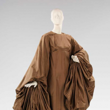<p>Madame Alix Grès (French, 1903–1993). <i>Evening Dress</i>, 1969. Taupe silk paper taffeta. Brooklyn Museum Costume Collection at The Metropolitan Museum of Art, Gift of the Brooklyn Museum, 2009; Gift of Mrs. William Randolph Hearst, Jr., 1988 (2009.300.1373)</p>