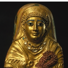 <p><i>Mummy Cartonnage of a Woman</i>. Egypt, from Hawara. Roman Period, 1st century <small>C.E.</small> Linen, gilded gesso, glass, faience, 22<sup>11</sup>&frasl;<sub>16</sub> x 14<sup>5</sup>&frasl;<sub>8</sub> x 7<sup>1</sup>&frasl;<sub>2</sub> in. (57.6 &times; 37.2 &times; 19 cm). Brooklyn Museum, Charles Edwin Wilbour Fund, 69.35</p>