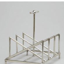 <p>Christopher Dresser (English, 1834–1904). <i>Toast Rack</i>, circa 1880. Silver, 5<sup>3</sup>⁄<sub>8</sub> x 5<sup>1</sup>⁄<sub>4</sub> x 4<sup>1</sup>⁄<sub>4</sub> in. (13.7 &#215; 13.3 &#215; 10.8 cm). Manufactured by Tiffany &amp; Company (New York, active 1853–present). Brooklyn Museum, Gift of Marie Bernice Bitzer, by exchange, 1997.114</p>