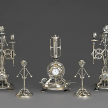 <p>Guilmet Cie (active 1861–1910). <i>Five-Piece Clock Garniture</i>, circa 1885. Silvered bronze, 9<sup>1</sup>⁄<sub>4</sub> x 4<sup>1</sup>⁄<sub>2</sub> x 4<sup>1</sup>⁄<sub>2</sub> in. (23.5 × 11.4 × 11.4 cm). Brooklyn Museum, Gift of Marcus S. Friedlander, by exchange, 2009.49.1-5</p>