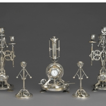 <p>Guilmet Cie (active 1861&ndash;1910). <i>Five-Piece Clock Garniture</i>, circa 1885. Silvered bronze, 9<sup>1</sup>&frasl;<sub>4</sub> x 4<sup>1</sup>&frasl;<sub>2</sub> x 4<sup>1</sup>&frasl;<sub>2</sub> in. (23.5 &times; 11.4 &times; 11.4 cm). Brooklyn Museum, Gift of Marcus S. Friedlander, by exchange, 2009.49.1-5</p>