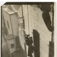 <p><i>Djuna Barnes and unidentified fireman, dangling from a rope beside a building</i>, October 1914. Gelatin silver photograph. Djuna Barnes Papers, Special Collections, University of Maryland Libraries</p>