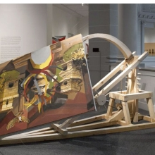 "<p>Caitlin Cherry (American, b. 1987). <i>Dual-Firing Trebuchet Artcraft ""Virgin On The Rocks,""</i> 2013. Brooklyn Museum installation. Oil on canvas with wood and rope construction, 108 &#215; 108 &#215; 48 in. (274.32 &#215; 274.32 &#215; 121.92 cm); overall dimensions variable. Courtesy of the artist (Photo: Brooklyn Museum)</p>"