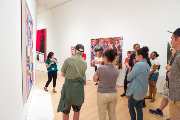<p>A group of people, many with their arms crossed, stand in a white gallery with brightly colored works against the walls. A teaching artist in a teal shirt points towards the artwork behind her as she looks out to the group.</p>