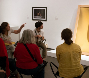 <p>Six people sit on stools in a white museum space. One person points toward a shadowy, yellow, abstract form in a wooden frame against the wall and the rest gaze towards it.</p>