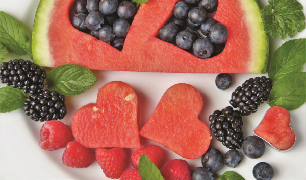 <p>Watermelon cut into hearts and arranged on a table with berries</p>