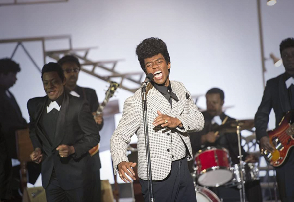 <p>Still from the film Get on Up, showing actor Chadwick Boseman playing James Brown singing on stage with a band </p>