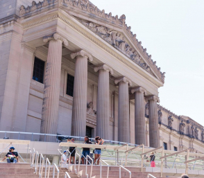<p>Visitors wear masks and sit on the steps of the Museum plaza</p>