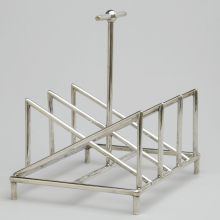 <p>Christopher Dresser (English, 1834–1904). <i>Toast Rack</i>, circa 1880. Silver, 5<sup>3</sup>⁄<sub>8</sub> x 5<sup>1</sup>⁄<sub>4</sub> x 4<sup>1</sup>⁄<sub>4</sub> in. (13.7 × 13.3 × 10.8 cm). Manufactured by Tiffany & Company (New York, active 1853–present). Brooklyn Museum, Gift of Marie Bernice Bitzer, by exchange, 1997.114</p>