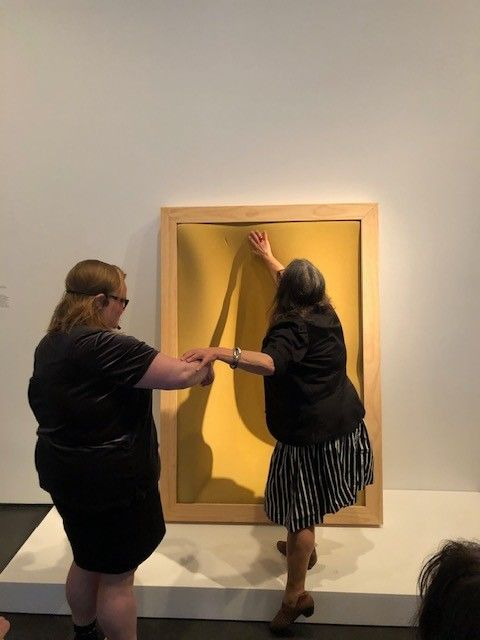 <p>A woman steps onto a white platform and reaches upward to touch a yellow foam compressed inside a wooden frame. Another woman stands on the ground, offering the assist of her elbow.</p>