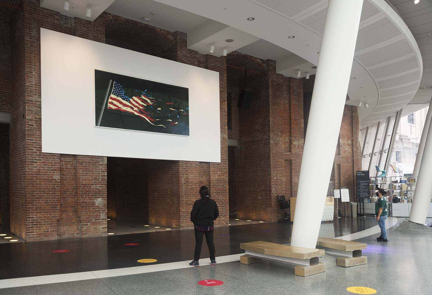 <p>Installation view of the Museum lobby featuring Ed Ruscha's painting OUR FLAG.</p>