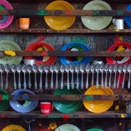 <p>Marcel Pinas (b. Suriname 1971). <em>Kuku (Kitchen)</em>, 2005. Plastic plates, aluminum spoons, cups, wood shelves; 59 &times; 59 &times; 8<sup>5</sup>&frasl;<sub>8</sub> in. (150 &times; 150 &times; 22 cm). Courtesy of the artist</p>