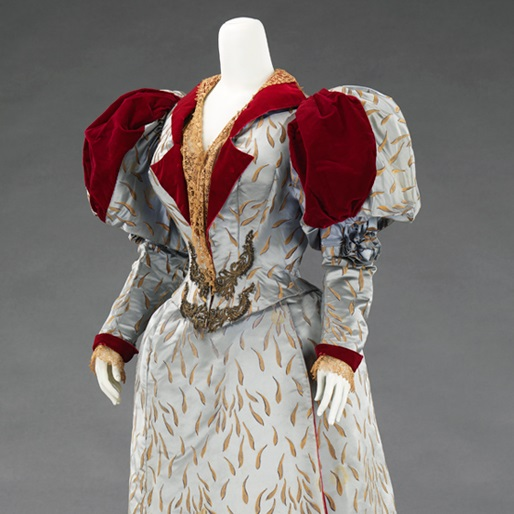 <p>Charles Frederick Worth (French, born Britain, 1825–1895) or Jean-Philippe Worth (French, 1856–1926). <i>Evening Dress</i>, 1893. Blue silk satin patterned with gold chrysanthemum petals, red silk velvet, ecru machine-made lace, beadwork, and metallic passementerie. Brooklyn Museum Costume Collection at The Metropolitan Museum of Art, Gift of the Brooklyn Museum, 2009; Formerly Collection of Emma Frink Perry; Gift of Edith Gardiner, 1926 (2009.300.622a–c)</p>