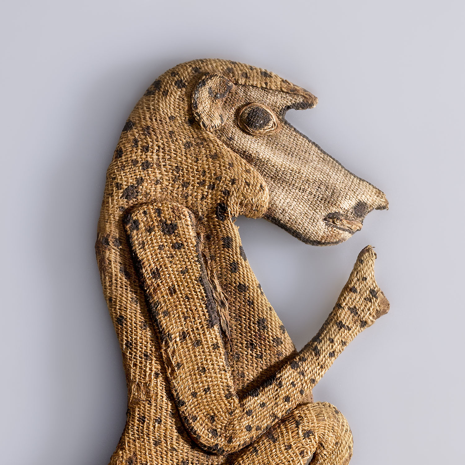 Baboon Appliqué from an Animal Mummy. Possibly from Saqqara, Egypt. Ptolemaic Period, 305–30 B.C.E. Linen, 51/2 x 23/8 in. (14.2 x 5.6 cm). Brooklyn Museum; Charles Edwin Wilbour Fund, 37.272E. (Photo: Gavin Ashworth, Brooklyn Museum)