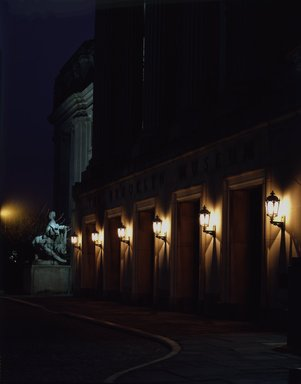 """<em>""""Brooklyn Museum: exterior. View of the Central section entrance at night from the entrance pathway, showing lit lamps and Manhattan statue in the background, 1990.""""</em>, 1990. Color transparency 4x5in, 4 x 5in (10.2 x 12.7 cm). Brooklyn Museum, Museum building. (Photo: Brooklyn Museum, S06_BEEi140.jpg"""