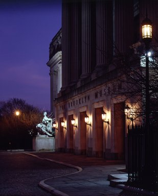 "<em>""Brooklyn Museum: exterior. View of the Central section entrance at night from the entrance pathway, showing lit lamps and Manhattan statue in the background, 1990.""</em>, 1990. Color transparency 4x5in, 4 x 5in (10.2 x 12.7 cm). Brooklyn Museum, Museum building. (Photo: Brooklyn Museum, S06_BEEi142.jpg"