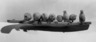 Carving of nine walruses on an ice floe