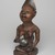 Yombe artist. <em>Figure of Mother and Child (Phemba)</em>, 19th century. Wood, glass, upholstery studs, metal, metal and glass buttons, resin, 11 x 5 x 4 1/2 in. (27.9 x 12.7 x 11.4 cm). Brooklyn Museum, Museum Expedition 1922, Robert B. Woodward Memorial Fund, 22.1138. Creative Commons-BY (Photo: , 22.1138_threequarter_left_PS9_PS9.jpg)