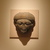 <em>Face from the Lid of a Sarcophagus</em>, ca. 1336-1250 B.C.E. Sandstone, 18 × 17 × 5 in. (45.7 × 43.2 × 12.7 cm). Brooklyn Museum, Charles Edwin Wilbour Fund, 85.166. Creative Commons-BY (Photo: Brooklyn Museum, CUR.85.166_wwg8.jpg)