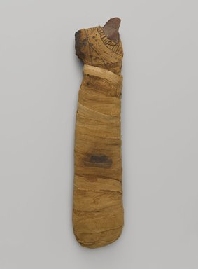 <em>Mummified Cat</em>, 305 B.C.E.-395 C.E. Animal remains, linen, pigment, 14 7/8 × 2 3/4 × 3 3/4 in. (37.8 × 7 × 9.5 cm). Brooklyn Museum, Charles Edwin Wilbour Fund, 05.307. Creative Commons-BY (Photo: Brooklyn Museum, 05.307_PS9.jpg)
