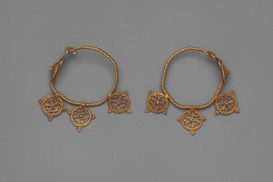 <em>Earrings with Open Work Wheels</em>, 6th century C.E. Gold, each earring: 2 3/8 x 9/16 in. (6 x 1.5 cm). Brooklyn Museum, Ella C. Woodward Memorial Fund, 05.439a-b. Creative Commons-BY (Photo: Brooklyn Museum, 05.439a-b.jpg)