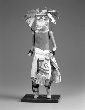 She-we-na (Zuni Pueblo). <em>Kachina Doll (Kan-nachu)</em>, late 19th century. Wood,pigment, textile, yarn, string, feathers, 15 13/16 x 4 1/2 x 3 11/16 in. (40.2 x 11.4 x 9.4 cm). Brooklyn Museum, Museum Expedition 1907, Museum Collection Fund, 07.467.8437. Creative Commons-BY (Photo: Brooklyn Museum, 07.467.8437_bw.jpg)