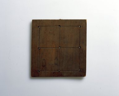 Ainu. <em>Square Board with Pins for Game</em>. Wood, 1/2 x 8 1/8 x 7 13/16 in. (1.3 x 20.7 x 19.8 cm). Brooklyn Museum, Gift of Herman Stutzer, 12.650. Creative Commons-BY (Photo: North American Ainu Documentation Project, Yoshiburo Kotani, 1990-92, 12.650_Ainu_project.jpg)
