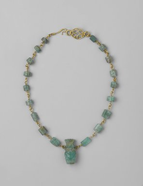 <em>Necklace</em>, 1st century C.E. Gold, beryl, silver, Necklace: 13 9/16 in. (34.4 cm) long; Bes figure: 1 x 7.16 in. (2.6 x 1.1 cm). Brooklyn Museum, Gift of Evangeline Wilbour Blashfield, Theodora Wilbour, and Victor Wilbour honoring the wishes of their mother, Charlotte Beebe Wilbour, as a memorial to their father, Charles Edwin Wilbour, 16.149. Creative Commons-BY (Photo: Brooklyn Museum, 16.149_PS2.jpg)