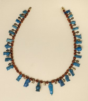 <em>Necklace with Bes and Taweret Pendants</em>, ca. 1539-1292 B.C.E. Gold, faience, carnelian, 1 1/16 x 14 15/16 in. (2.7 x 38 cm). Brooklyn Museum, Gift of Evangeline Wilbour Blashfield, Theodora Wilbour, and Victor Wilbour honoring the wishes of their mother, Charlotte Beebe Wilbour, as a memorial to their father Charles Edwin Wilbour, 16.580.201. Creative Commons-BY (Photo: Brooklyn Museum, 16.580.201_PS4.jpg)