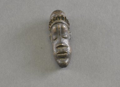 Bassa. <em>Personal Miniature Mask</em>, 20th century. Wood, 2 1/2 x 1in. (6.4 x 2.5cm). Brooklyn Museum, Gift of Dr. Svend E. Holsoe, 1993.175.7. Creative Commons-BY (Photo: Brooklyn Museum, 1993.175.7_front_PS5.jpg)