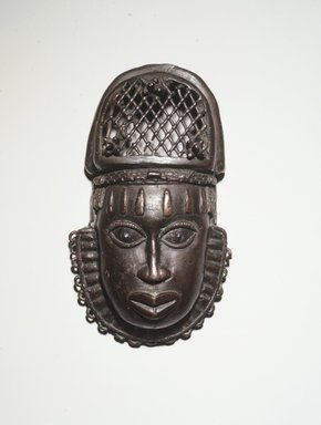 Edo. <em>Pendant Mask (Uhunmwun-ekue)</em>, 19th century. Copper alloy, iron, 7 3/4 × 4 5/16 × 1 3/4 in. (19.7 × 11 × 4.5 cm). Brooklyn Museum, Gift of Dorothy Robbins, 1993.180.15. Creative Commons-BY (Photo: Brooklyn Museum, 1993.180.15_transp5318.jpg)