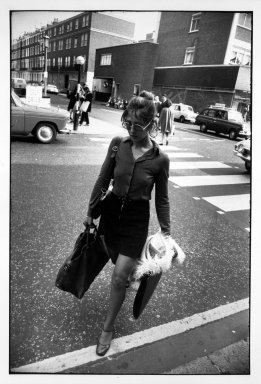 Garry Winogrand (American, 1928-1984). <em>Untitled (Woman with Purse and Portfolio Crossing the Street), from Women are Beautiful Series</em>. Gelatin silver photograph, sheet: 14 x 11 in. (35.5 x 27.9 cm). Brooklyn Museum, Gift of Mitchell F. Deutsch, 1995.206.13. © artist or artist's estate (Photo: Brooklyn Museum, 1995.206.13_bw.jpg)