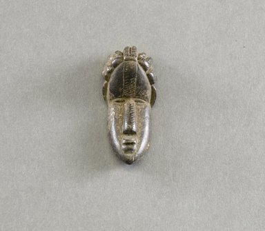 Bassa. <em>Personal Miniature Mask</em>, 20th century. Wood, 2 5/8 x 1 1/8 x 7/8 in. (6.7 x 2.9 x 2.2 cm). Brooklyn Museum, Gift of Blake Robinson, 1995.7.56. Creative Commons-BY (Photo: Brooklyn Museum, 1995.7.56_front_PS5.jpg)