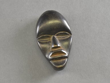 Mano. <em>Personal Miniature Mask</em>, 20th century. Wood, 3 1/2 x 2 x 7/8in. (8.9 x 5.1 x 2.2cm). Brooklyn Museum, Gift of Blake Robinson, 1995.7.71. Creative Commons-BY (Photo: Brooklyn Museum, 1995.7.71_front_PS5.jpg)