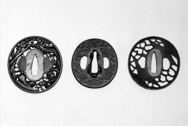 <em>Sword Guard (Tsuba)</em>, 17th-18th century. Pierced and carved brass with gold overlay; holes plugged with shakudo or shibuichi and pitch, 2 7/8 x 2 3/4 in.  (7.3 x 7.0 cm). Brooklyn Museum, Gift of Dr. and Mrs. Barry Brumberg, 1999.98.3. Creative Commons-BY (Photo: , 1995.9.8_1999.98.3_1999.98.4_view1_bw.jpg)