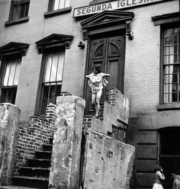 Vivian Cherry (American, 1920-2019). <em>Spanish Harlem (Young Girl on Stairs Holding Her Skirt Up)</em>, 1947. Gelatin silver photograph (vintage), 10 15/16 x 10 in. (32.9 x 25.4 cm). Brooklyn Museum, Gift of Steven Schmidt, 1996.241.42. © artist or artist's estate (Photo: Brooklyn Museum, 1996.241.42_bw.jpg)