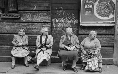 Vivian Cherry (American, 1920-2019). <em>Lower East Side N.Y.C (Heinz Beans, Swastika on Wall Beyond Four Seated Women)</em>, ca 1950s. Gelatin silver photograph (vintage), image: 8 1/2 x 13 1/2 in. (21.6 x 34.3 cm). Brooklyn Museum, Gift of Steven Schmidt, 1996.241.9. © artist or artist's estate (Photo: Brooklyn Museum, 1996.241.9_bw.jpg)