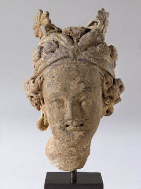 <em>Head of Divine Attendant</em>, ca. 4th century or earlier. Molded terracotta with applied stamped motifs and traces of polychrome, 4 1/8 x 2 3/4 x 2 1/2 in. Brooklyn Museum, Purchase gift of Dr. Bertram H. Schaffner, 1996.67. Creative Commons-BY (Photo: Brooklyn Museum, 1996.67_PS9.jpg)