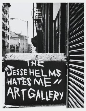 "Arthur Mones (American, 1919-1998). <em>New York, Soho (The ""Jesse Helms Hates Me"" ""Art Gallery"")</em>, 1990. Gelatin silver photograph, sheet: 14 x 10 3/4 in. (35.6 x 27.2 cm). Brooklyn Museum, Gift of the artist, 1997.162.2. © artist or artist's estate (Photo: Brooklyn Museum, 1997.162.2_PS4.jpg)"
