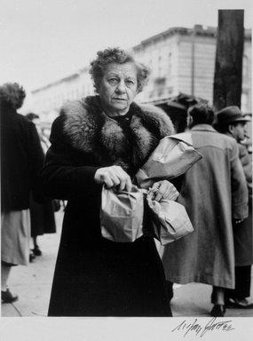 N. Jay Jaffee (American, 1921-1999). <em>Woman with Paper Bags (Blake Avenue)</em>, 1951; printed 1995. Selenium-toned gelatin silver photograph, image: 6 11/16 x 5 1/2 in. (17 x 14 cm). Brooklyn Museum, Gift of Paula W. Hackeling, 1997.164.27. © artist or artist's estate (Photo: Brooklyn Museum, 1997.164.27_bw.jpg)