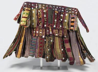 Yorùbá. <em>Egúngún Masquerade Dance Costume (paka egúngún)</em>, ca. 1920-1948. Cotton, wool, wood, silk, synthetic textiles (including viscose rayon and acetate), indigo, and aluminum, est.: 55 x 6 x 63 in. (139.7 x 15.2 x 160 cm). Brooklyn Museum, Gift of Sam Hilu, 1998.125. Creative Commons-BY (Photo: , 1998.125_front_PS11.jpg)