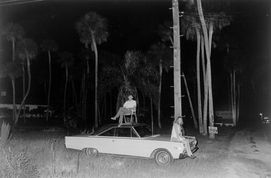 Joel Meyerowitz (American, born 1938). <em>Cape Canaveral, Moon Launch (Couple Sitting on Car)</em>, 1968. Gelatin silver photograph, Sheet: 11 x 14 in. (27.9 x 35.6 cm). Brooklyn Museum, Gift of Julian and Elaine Hyman, 2000.132.7. © artist or artist's estate (Photo: Brooklyn Museum, 2000.132.7_bw.jpg)