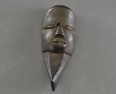 Mano. <em>Miniature Mask</em>, late 19th-early 20th century. Wood, aluminum, 6 x 2 3/8 x 1 7/8 in.  (15.2 x 6.0 x 4.8 cm). Brooklyn Museum, Gift of Blake Robinson, 2000.70.4. Creative Commons-BY (Photo: Brooklyn Museum, 2000.70.4_front.PS5.jpg)