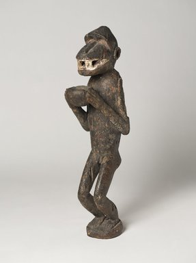 Baule. <em>Figure of a Monkey, possibly for Mbra</em>, late 19th or early 20th century. Wood, pigment, sacrificial material, 22 x 5 1/4 x 7 3/4 in.  (55.9 x 13.3 x 19.7 cm). Brooklyn Museum, Carll H. de Silver Fund, 2001.48. Creative Commons-BY (Photo: , 2001.48_threequarter_PS9.jpg)