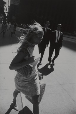 Garry Winogrand (American, 1928-1984). <em>[Untitled] (Woman with Long Hair Wrapped Under her Neck on the Sidewalk Walking)</em>, 1965. Gelatin silver photograph, printed 1981, image: 12 × 8 3/4 in. (30.5 × 22.2 cm). Brooklyn Museum, Gift of Howard Ganek, 2001.74.2. © artist or artist's estate (Photo: , 2001.74.2_PS9.jpg)